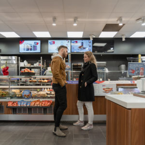 """OKQ8 - Quick To Go We are revisiting the forecourt store OKQ8 that is next to Landvetter airport in Gothenburg, where the new concept rollout called """"Quick To Go"""" started in 2014. """"Since this first store delivery, ROL Fredbergs have completed about 240 store deliveries to OKQ8 – updating their stores to the Quick To Go concept"""" – says Maria Sandberg, Project manager at ROL Fredbergs. """"I´m happy to find the store in such a good shape, after six years in use, it still looks very fresh"""", says Maria. During the intervening years OKQ8 and ROL Fredbergs have developed many updates and additions to the Quick to Go concept.  We had the chance to talk to Tobias Lindmark, Store concept & Brand experience developer for OKQ8, and asked him about our co-operation. He commented that, """"ROL Fredbergs is an important part of our development work. ROL Fredbergs adds a high level of expertise and the knowledge we seek in a partner rather than a supplier. With its broad knowledge, ROL Fredbergs adds both business understanding and customer benefit within our forecourt store network"""". What do you think is important in order to give the customer a positive experience in your store? """"With OKQ8's wide product range, it is important to always put the customer satisfaction first and always offer the best possible service, whether we talk about food, convenience, car hire, car wash or motorist products. Our customer service expertise guarantees the very best retail experience at our stations Tobias also said – """"We are constantly making improvements and updates. Credibility, customer satisfaction and sustainability are always on top of our mind. No concept is better than its followers, we are very proud to be able to present a complete retail chain with the same concept across all its stations in the near future. It proves the greatness of the brand OKQ8.""""  Maria explains how the retail concept update process often looks like. """"The retail concept process normally starts with an idea from OKQ8,"""